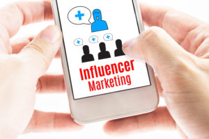 Close up Two hand holding smart phone with Influencer Marketing word and icons Digital concept.